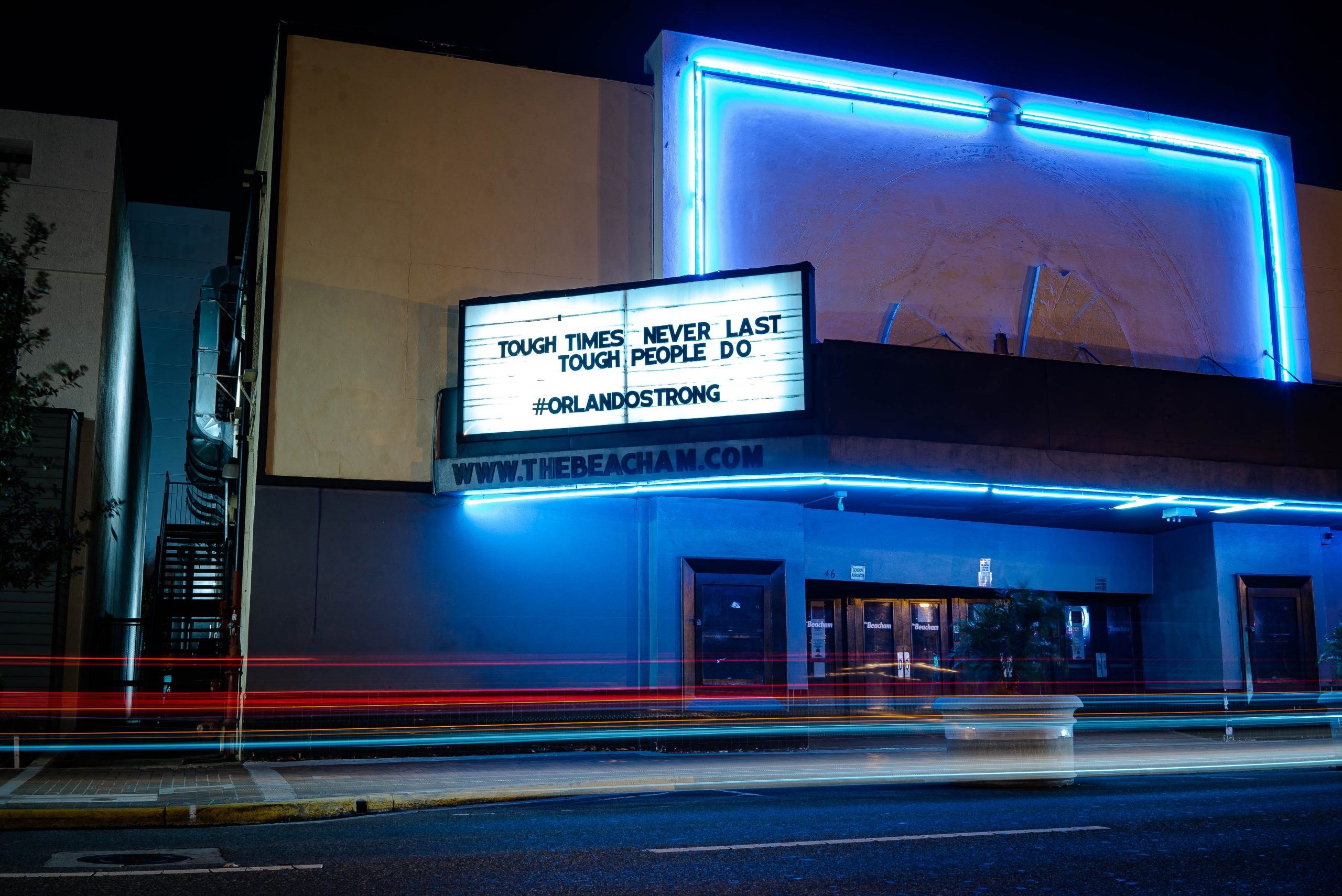 Tail lights streak past this night time photograph of a run down theatre, blue lights illuminate the doors, and a billboard above reads 'tough times don't last, tough people do' hashtag Orlando strong' How tough would they be if they new the ghosts under their feet.