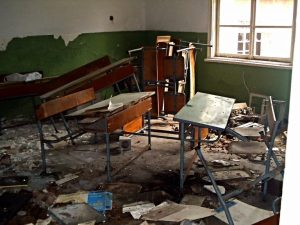 image shows desks strewn about an abandoned classroom