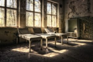 image shows an abandoned hospital room with ghastly beds
